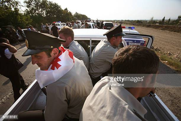 Georgian policemen wait for Russian peace keeping troops to let them pass the last checkpoint they control near Kharvaleti on the road from Tbilisi...