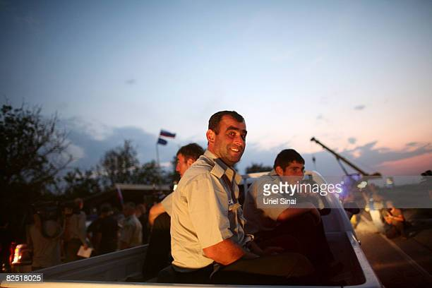 Georgian policemen wait in the back of a pickup truck for Russian peace keeping troops to let them pass the last checkpoint they control near...