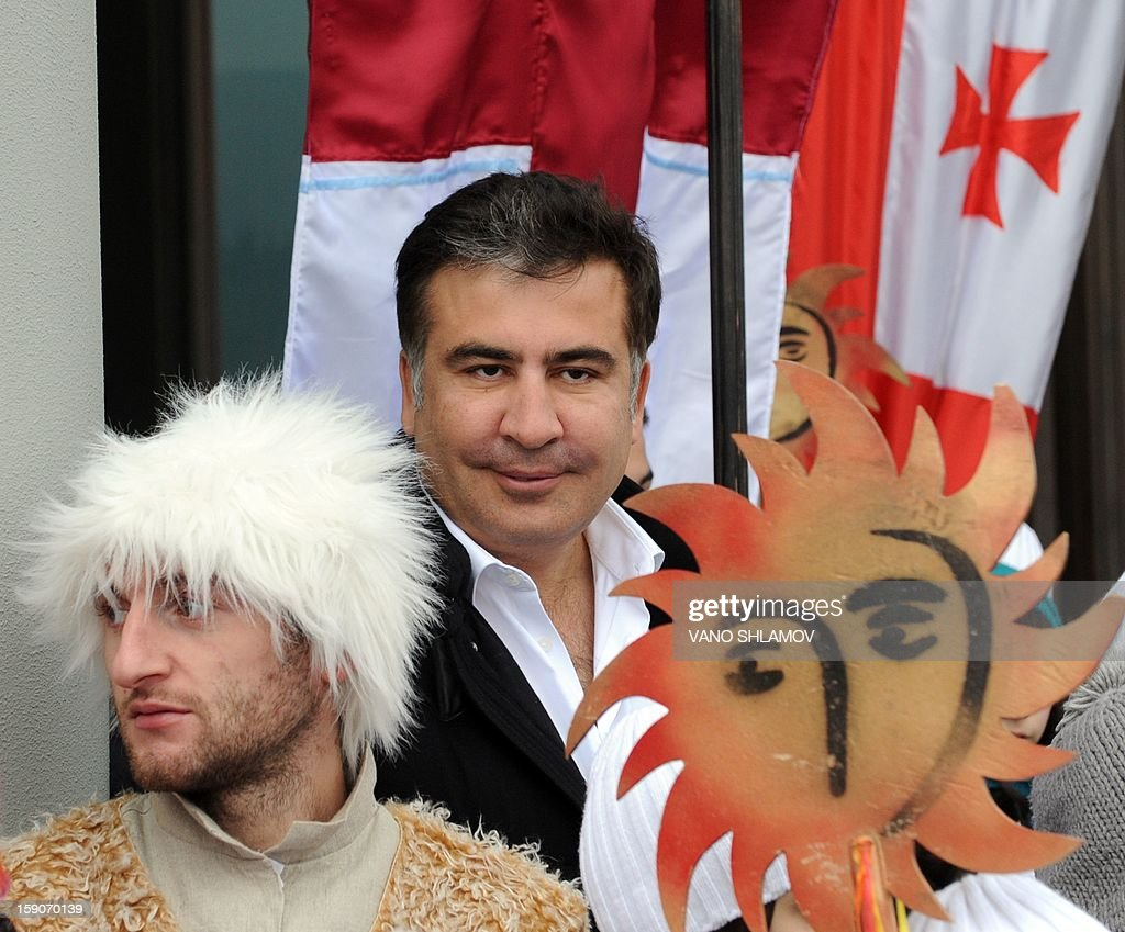 Georgian President Michael Saakashvili (C) attends a procession in Tbilisi on January 7, 2013 during the Christmas celebrations. Orthodox Christians celebrate Christmas on January 7 in the Middle East, Russia and other Orthodox churches that use the old Julian calendar instead of the 17th-century Gregorian calendar adopted by Catholics, Protestants, Greek Orthodox and commonly used in secular life around the world.