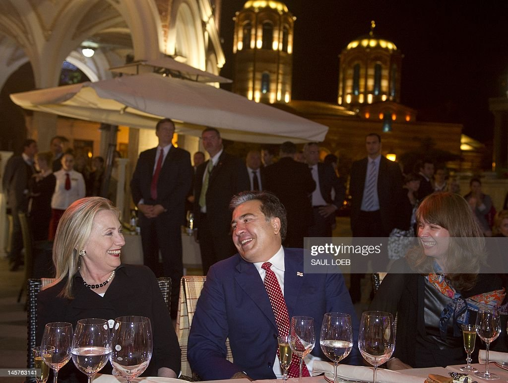 Georgian President Mikheil Saakashvili and his wife, Sandra Roelofs (R), along with US Secretary of State Hillary Clinton (L), attend a cultural performance at the Piazza in Batumi on June 5, 2012. AFP PHOTO / POOL / Saul LOEB