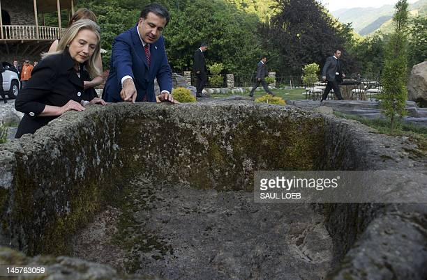 Georgian President Mikheil Saakashvili and US Secretary of State Hillary Clinton look at an ancient wine basin prior to dinner at Adjarian Wine House...