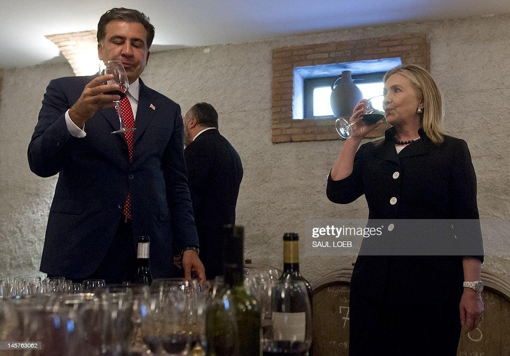 Georgian President Mikheil Saakashvili and US Secretary of State Hillary Clinton sample wine prior to dinner at Adjarian Wine House in Batumi on June 5, 2012. AFP PHOTO / POOL / Saul LOEB