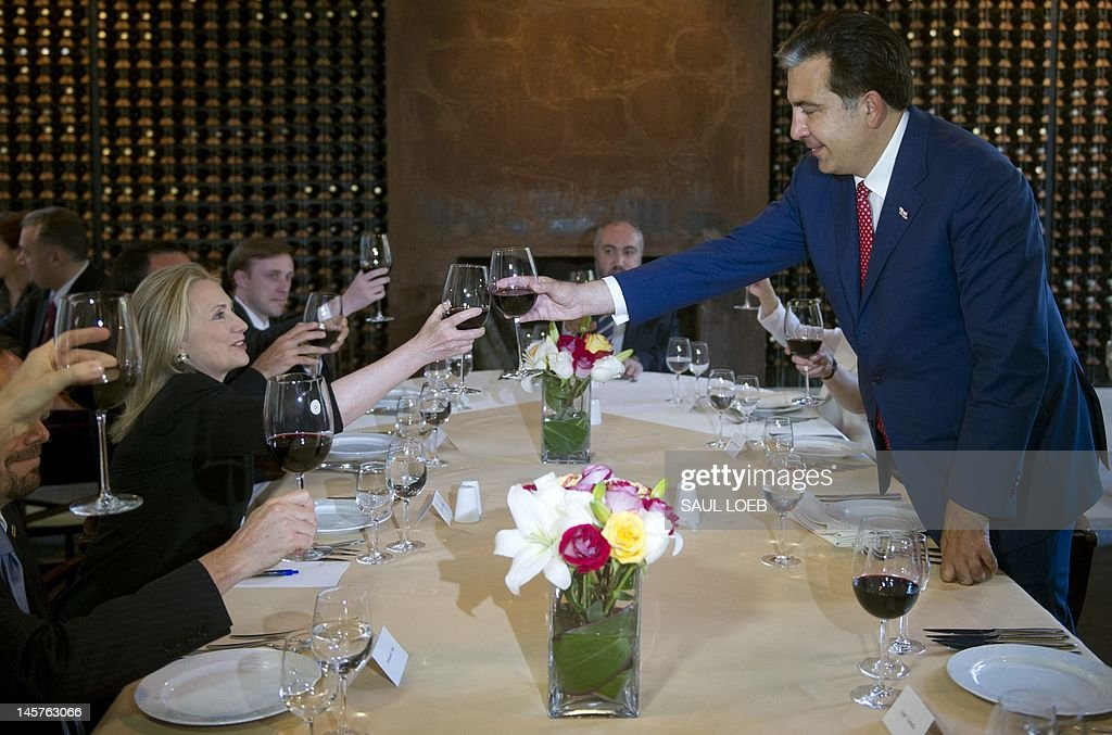 Georgian President Mikheil Saakashvili (R) and US Secretary of State Hillary Clinton toast during dinner at Adjarian Wine House in Batumi on June 5, 2012. AFP PHOTO / POOL / Saul LOEB