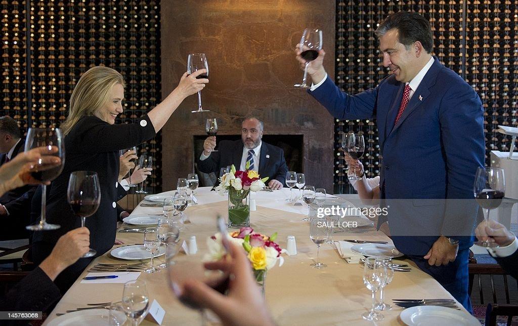 Georgian President Mikheil Saakashvili (R) and US Secretary of State Hillary Clinton toast during dinner at Adjarian Wine House in Batumi on June 5, 2012. AFP PHOTO / POOL / Saul LOEB