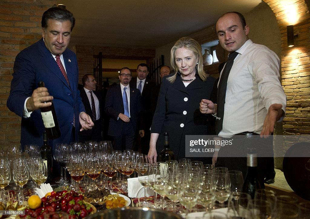 Georgian President Mikheil Saakashvili (L) and US Secretary of State Hillary Clinton (C) sample wine in a wine cellar prior to dinner at Adjarian Wine House in Batumi on June 5, 2012. AFP PHOTO / POOL / Saul LOEB