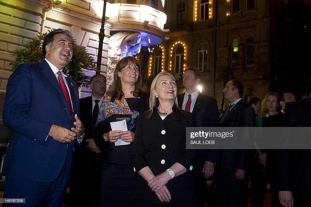 Georgian President Mikheil Saakashvili, his wife Sandra Roelofs (C) and US Secretary of State Hillary Clinton (R), walk through the streets of Batumi after attending a cultural dancing and singing performance at the Piazza in Batumi on June 5, 2012. Clinton has used her two-day visit to this Black Sea port to assure Georgians of unwavering US support for its territorial integrity and to call on Russia to pull back troops in two breakaway Georgian regions that were the focus of the 2008 war. AFP PHOTO / POOL / Saul LOEB