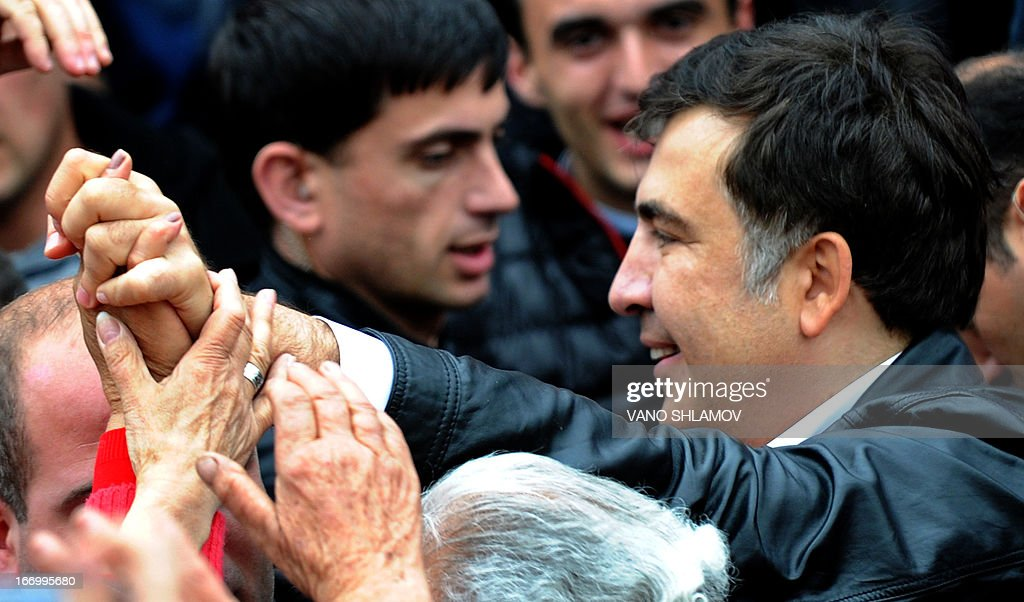 Georgian President Mikheil Saakashvili shakes hands with supporters during a rally in central Tbilisi on April 19, 2013. Over 10,000 supporters of Georgian President Mikheil Saakashvili took to the streets in the capital Friday in a first mass rally since his party's defeat at parliamentary elections last year.