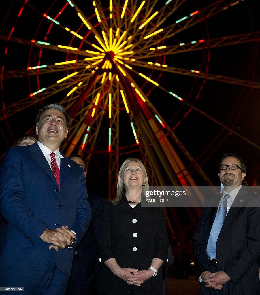 Georgian President Mikheil Saakashvili (L), US Secretary of State Hillary Clinton and Philip Gordon (C), US Assistant Secretary of State for Europe and Eurasian Affairs, stop in front of a Ferris Wheel at Batumis Bulvari as they walk through the streets of Batumi on June 5, 2012, following a cultural dancing and singing performance at the Piazza. AFP PHOTO / POOL / Saul LOEB