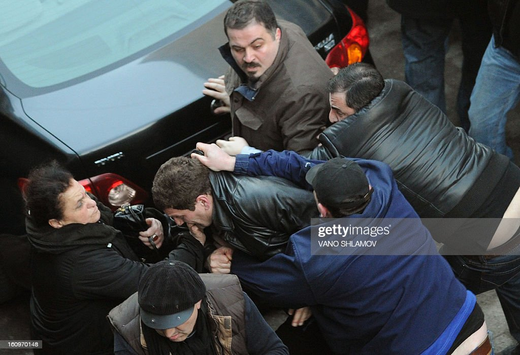 Georgian President Mikheil Saakashvili's allies scuffles with protesters in Tbilisi , on February 8, 2013. An angry crowd of around 300 protesters aimed today punches and kicks at the mayor of Tbilisi and several lawmakers from President Mikheil Saakashvili's party in the Georgian capital, hours before the president was to give his annual state of the nation address. AFP PHOTO / VANO SHLAMOV