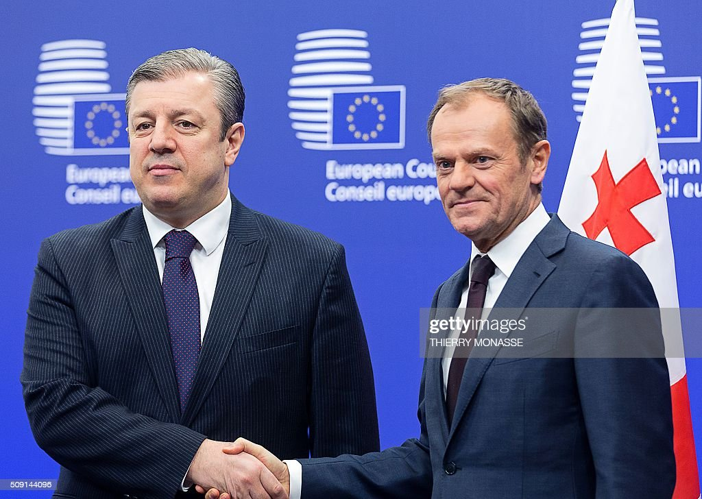 Georgian Prime Minister Giorgi Kvirikashvili (L) is welcomed by European Council President Donald Tusk (R) prior to a bilateral meeting at the European Council headquarters in Brussels on February 9, 2016. AFP PHOTO / THIERRY MONASSE / AFP / THIERRY MONASSE