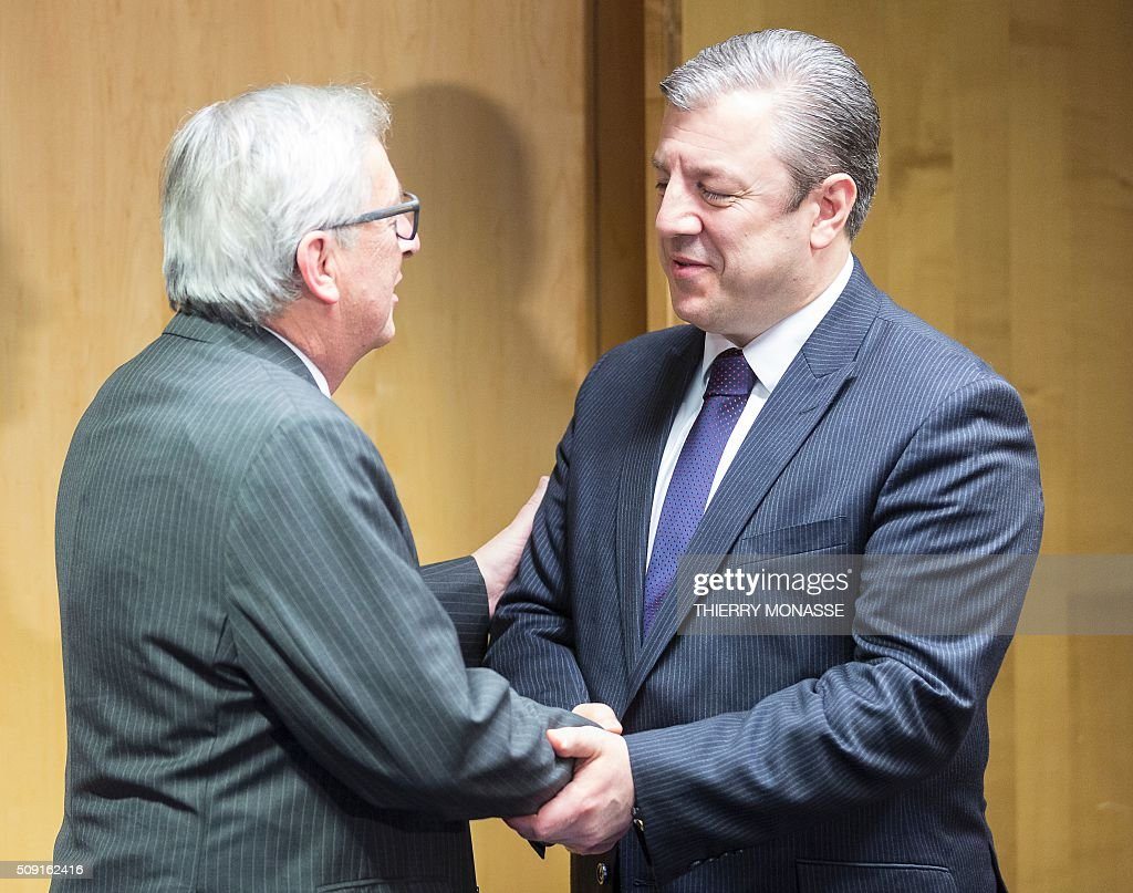 Georgian Prime Minister Giorgi Kvirikashvili (R) is welcomed by European Commission President Jean-Claude Juncker (L) prior to a bilateral meeting at the European Council headquarters in Brussels on February 9, 2016. / AFP / Thierry Monasse