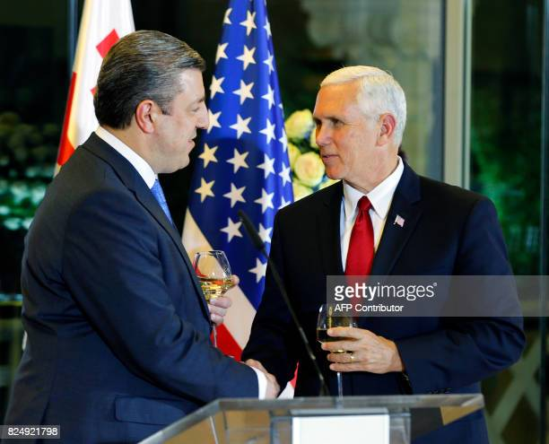 Georgian Prime Minister Giorgi Kvirikashvili shakes hands with US Vice President Mike Pence during an official dinner in Tbilisi Georgia on July 31...