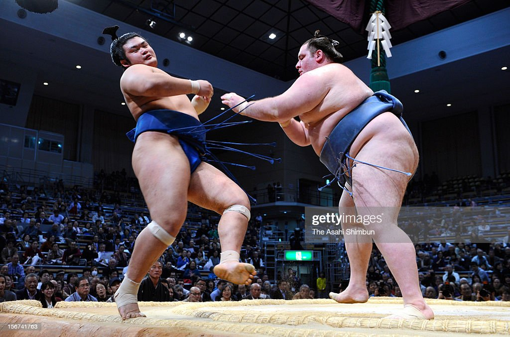Georgian sumo wrestler Gagamaru (R) pokes out Chiyonokuni from the ring during day nine of the Grand Sumo November Tournament at Fukuoka Convention Center on November 19, 2012 in Fukuoka, Japan.