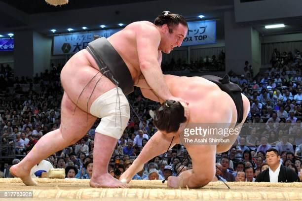 Georgian wrestler Tochinoshin throws Mongolian wrestler Ichinojo to win during day ten of the Grand Sumo Nagoya Torunament at Aichi Prefecture...