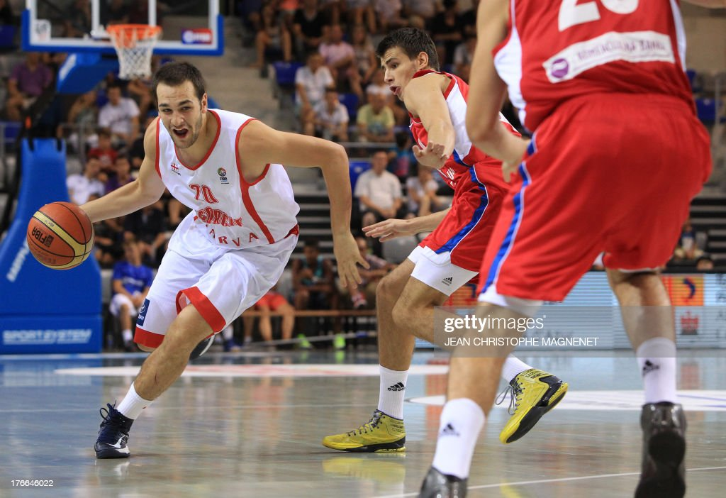 Georgia's Duda Sanadze (L) passes by Serbia's Nemanja Dangubic (C) during a friendly basketball match between Serbia and Georgia on August 16, 2013 in Antibes, southeastern France as part of the preparation for the 2013 EuroBasket in Slovenia. AFP PHOTO / JEAN CHRISTOPHE MAGNENET