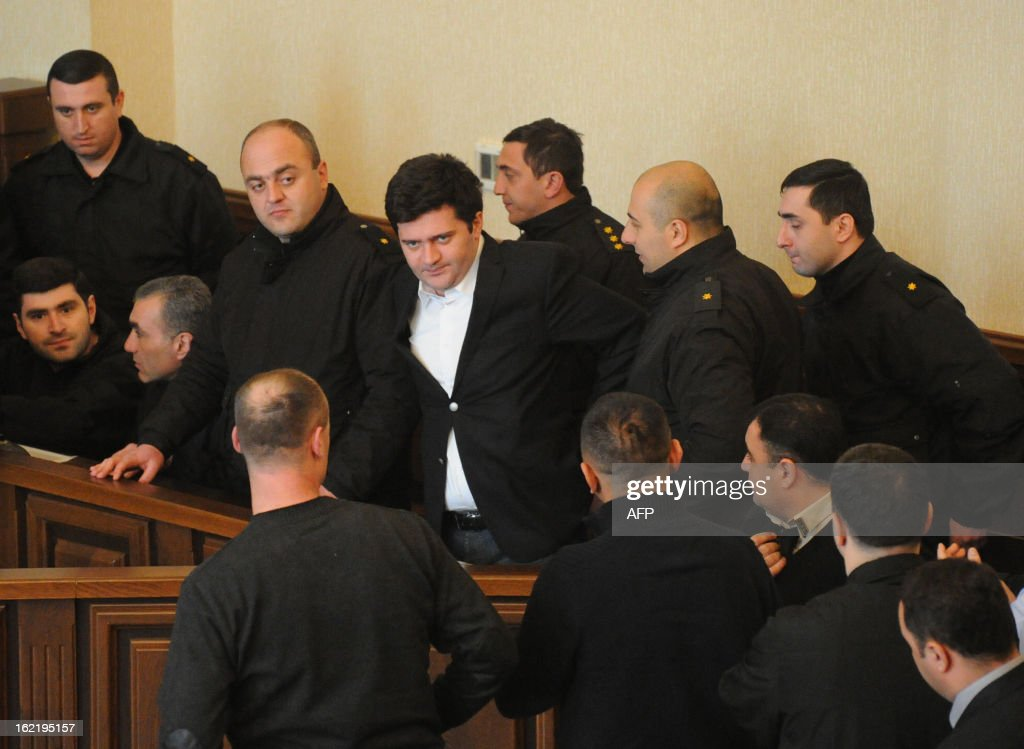 Georgia's former defense, prison and interior minister Bacho Akhalaia (C) arrives a court in the capital Tbilisi, on February 20, 2013. Tbilisi City Court held today pretrial hearing in the case against President Mikheil Saakashvili's loyalist Bacho Akhalaia and other former government officials, the Georgian media reported. AFP PHOTO / POOL / IRAKLI GEDENIDZE