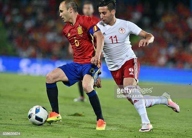 Georgia's forward Giorgi Chanturia vies for the ball with Spain's midfielder Andres Iniesta during the EURO 2016 friendly football match Spain vs...