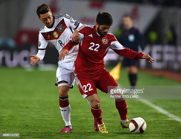 Georgia´s Giorgi Navalovski and Germany's midfielder Mesut Oezil vie for the ball during the Euro 2016 qualifying football match between Georgia and...
