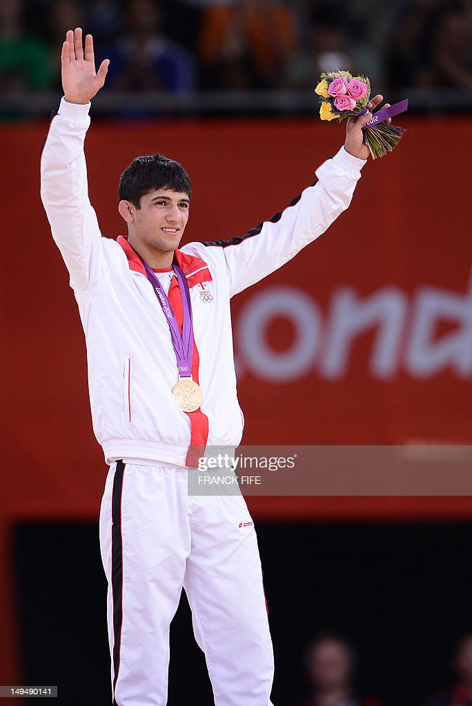 Georgia's gold medalist Lasha Shavdatuashvili celebrates on the podium of the men's 66kg contest of the judo event at the London 2012 Olympic Games...