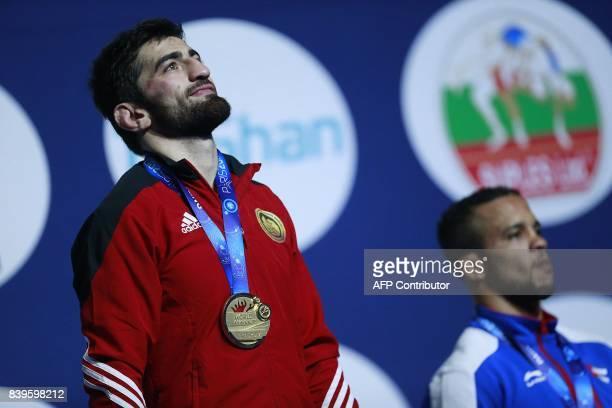 Georgia's gold medallist Zurabi Iakobishvili poses on the podium with Cuba's bronze medallist Alejandro Valdes Tobier during the medal ceremony for...