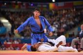 Georgia's Lasha Shavdatuashvili celebrates after winning against France's David Larose during their men's 66kg contest match of the judo event at the...