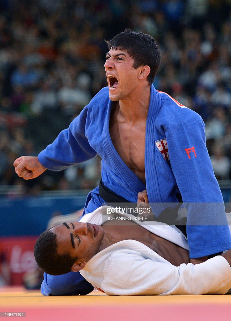 Georgia's Lasha Shavdatuashvili celebrates after winning against France's David Larose during their men's 66kg contest match of the judo event at the...