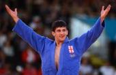 Georgia's Lasha Shavdatuashvili celebrates after winning against Hungary's Miklos Ungvari during their men's 66kg contest final match of the judo...