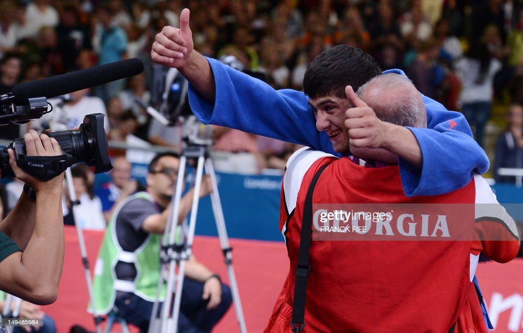 Georgia's Lasha Shavdatuashvili celebrates with a coach after winning against Hungary's Miklos Ungvari during their men's 66kg contest final match of...