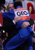 Georgia's Lasha Shavdatuashvili celebrates with his coach after winning against Hungary's Miklos Ungvari during their men's 66kg contest final match...