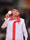 Georgia's Lasha Shavdatuashvili poses with his gold medalist on the podium of the men's 66kg contest of the judo event at the London 2012 Olympic...