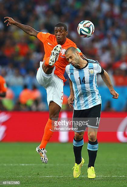Georginio Wijnaldum of the Netherlands and Javier Mascherano of Argentina compete for the ball during the 2014 FIFA World Cup Brazil Semi Final match...
