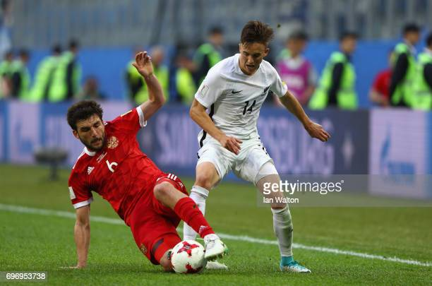 Georgy Dzhikya of Russia tackles Ryan Thomas of New Zealand during the FIFA Confederations Cup Russia 2017 Group A match between Russia and New...