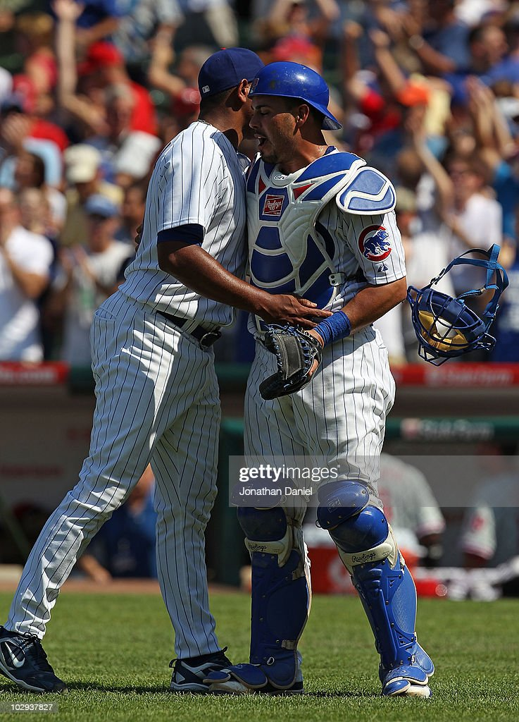 Geovany Soto #18 of the Chicago Cubs (R) hugs pitcher Carlos Marmol #49 and looses his face mask after a win over the Philadelphia Phillies at Wrigley Field on July 16, 2010 in Chicago, Illinois. The Cubs defeated the Phillies 4-3.