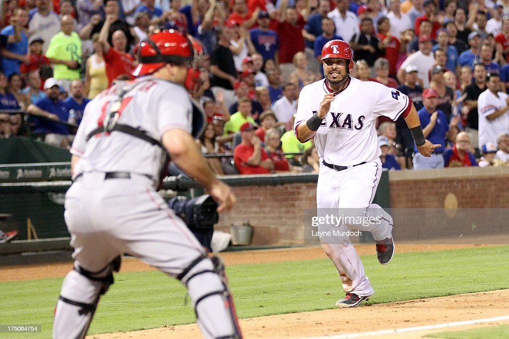 <a gi-track='captionPersonalityLinkClicked' href=/galleries/search?phrase=Geovany+Soto&family=editorial&specificpeople=743668 ng-click='$event.stopPropagation()'>Geovany Soto</a> #8 of the Texas Rangers runs home and scores as <a gi-track='captionPersonalityLinkClicked' href=/galleries/search?phrase=Chris+Iannetta&family=editorial&specificpeople=836137 ng-click='$event.stopPropagation()'>Chris Iannetta</a>, catcher for the Los Angeles Angels of Anaheim awaits the throw on July 30, 2013 at the Rangers Ballpark in Arlington in Arlington, Texas.