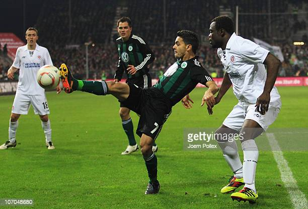 Gerald Asamoah of Hamburg and Josue of Wolfsburg battle for the ball during the Bundesliga match between FC St Pauli and VfL Wolfsburg at Millerntor...