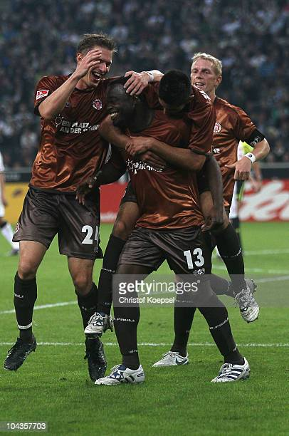 Gerald Asamoah of Pauli celebrates the first goal with Carsten Rothenbach of Pauli and Carlos Zambrano during the Bundesliga match between Borussia...