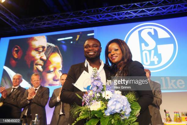 Gerald Asamoah reacts with his wife Linda after being awarded member of the Schalke 'Hall of fame' during the annual meeting of FC Schalke 04 at...