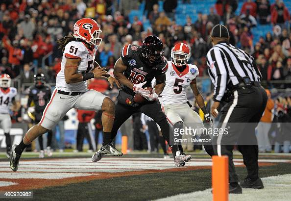 Gerald Christian of the Louisville Cardinals makes a touchdown catch between defenders Ramik Wilson and Damian Swann of the Georgia Bulldogs during...