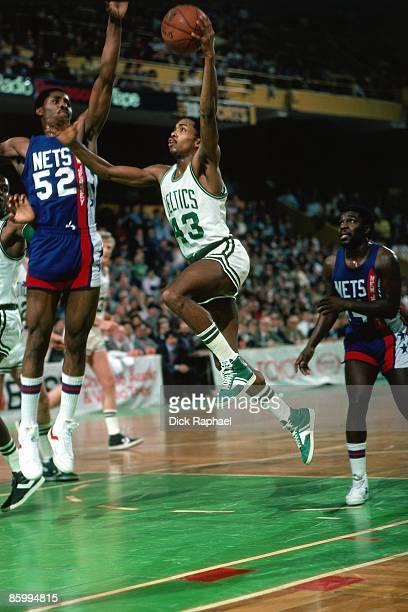 Gerald Henderson of the Boston Celtics drives the lane for a a laykup against Buck Williams of the New Jersey Nets during a game played in 1983 at...