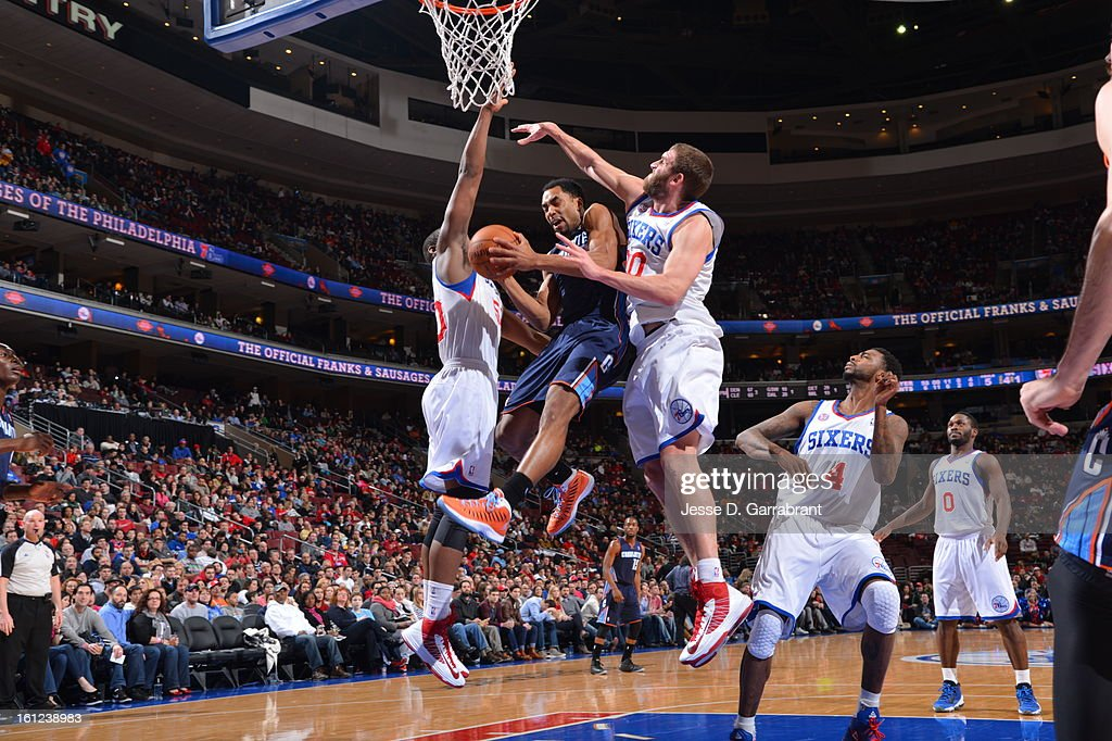 Gerald Henderson #9 of the Charlotte Bobcats goes to the basket against Lavoy Allen #50 and Spencer Hawes #00 of the Philadelphia 76ers during the game at the Wells Fargo Center on February 9, 2013 in Philadelphia, Pennsylvania.