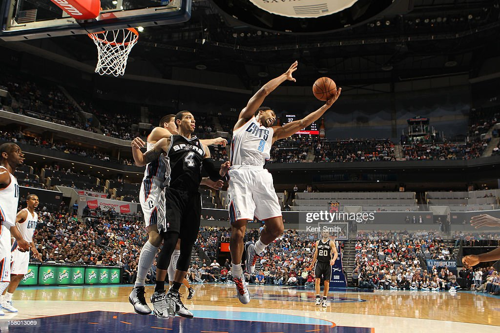 Gerald Henderson #9 of the Charlotte Bobcats grabs the rebound against Danny Green #4 of the San Antonio Spurs at the Time Warner Cable Arena on December 8, 2012 in Charlotte, North Carolina.