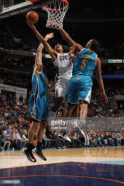 Gerald Henderson of the Charlotte Bobcats shoots against Dominic McGuire of the New Orleans Hornets at the Time Warner Cable Arena on December 29...