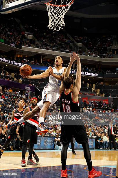 Gerald Henderson of the Charlotte Bobcats shoots against Victor Claver of the Portland Trail Blazers at the Time Warner Cable Arena on March 22 2014...