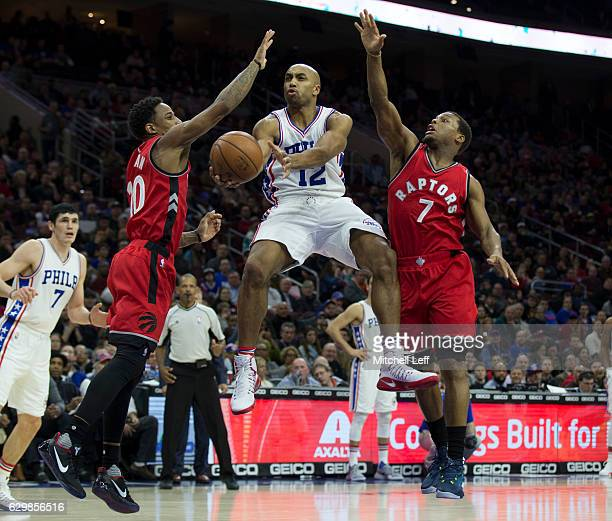 Gerald Henderson of the Philadelphia 76ers passes the ball around DeMar DeRozan and Kyle Lowry of the Toronto Raptors in the second quarter at Wells...