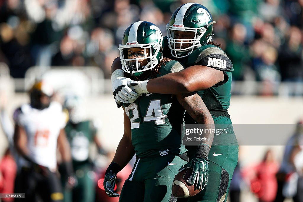 Gerald Holmes of the Michigan State Spartans gets a hug from Donavon Clark after rushing for a threeyard touchdown in the third quarter of the game...