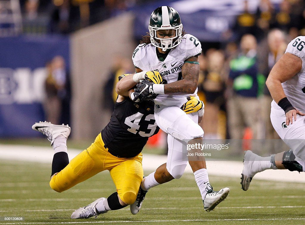 Gerald Holmes #24 of the Michigan State Spartans is dragged down by Josey Jewell #43 of the Iowa Hawkeyes in the Big Ten Championship at Lucas Oil Stadium on December 5, 2015 in Indianapolis, Indiana.