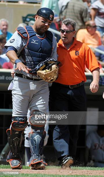 Gerald Laird of the Detroit Tigers is checked on by a trainer after getting hit by a foul tip in the eighth inning against the Minnesota Twins during...