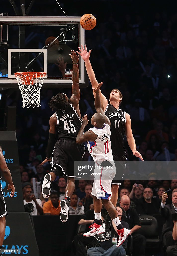 Gerald Wallace #45 and Brook Lopez #11 of the Brooklyn Nets combine to stop Jamal Crawford #11 of the Los Angeles Clippers at the Barclays Center on November 23, 2012 in the Brooklyn borough of New York City.