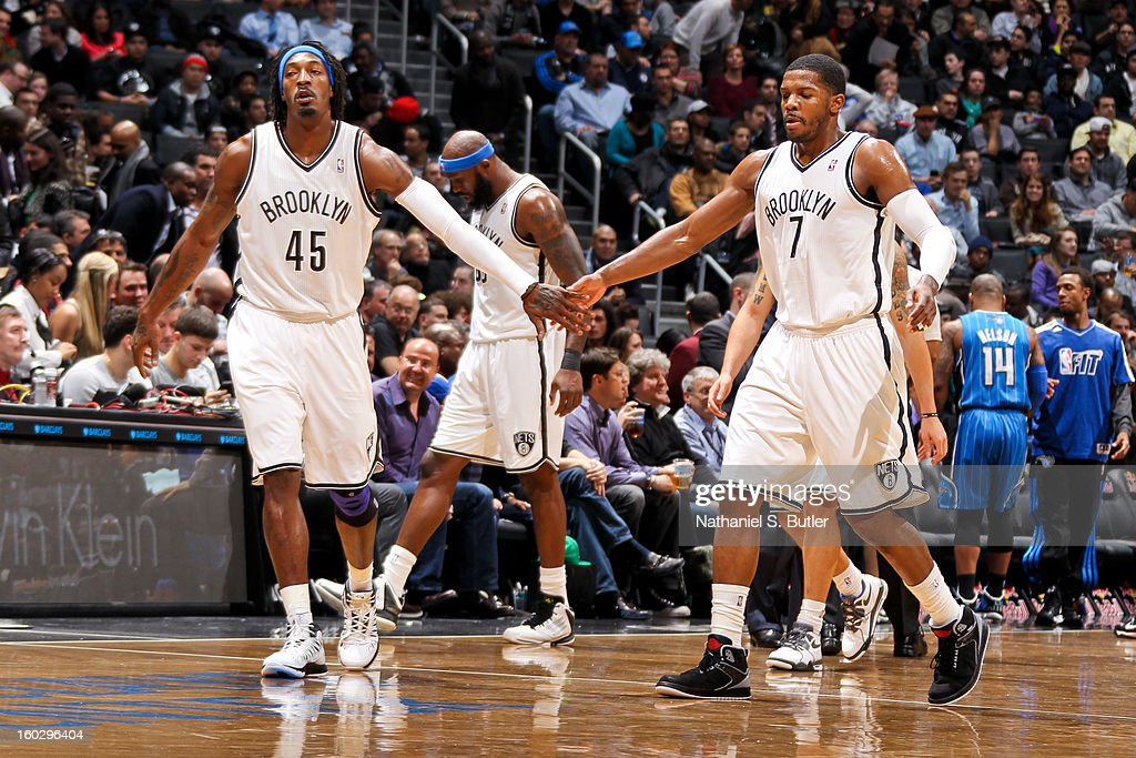 Gerald Wallace #45 and Joe Johnson #7 of the Brooklyn Nets celebrate during a game against the Orlando Magic on January 28, 2013 at the Barclays Center in the Brooklyn borough of New York City.