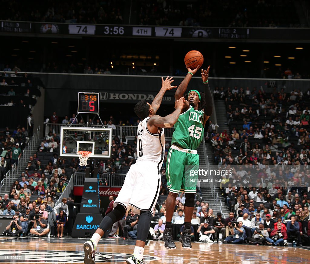 Gerald Wallace #45 of the Boston Celtics shoots against Gary Forbes #9 of the Brooklyn Nets during a preseason game at the Barclays Center on October 15, 2013 in the Brooklyn borough of New York City.